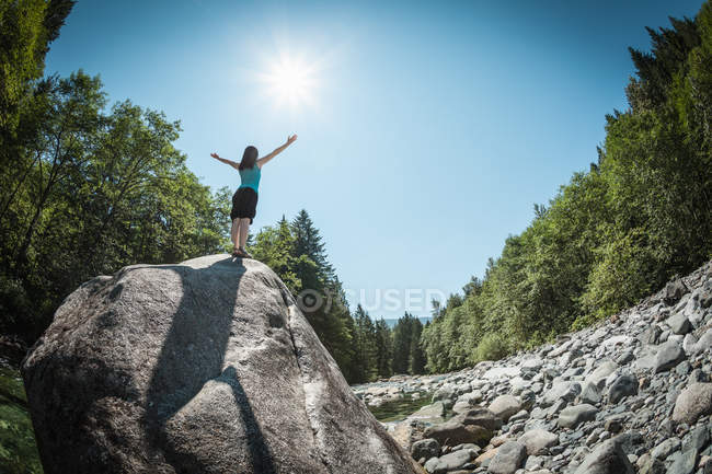 Woman with arms outstretched on rock — Stock Photo