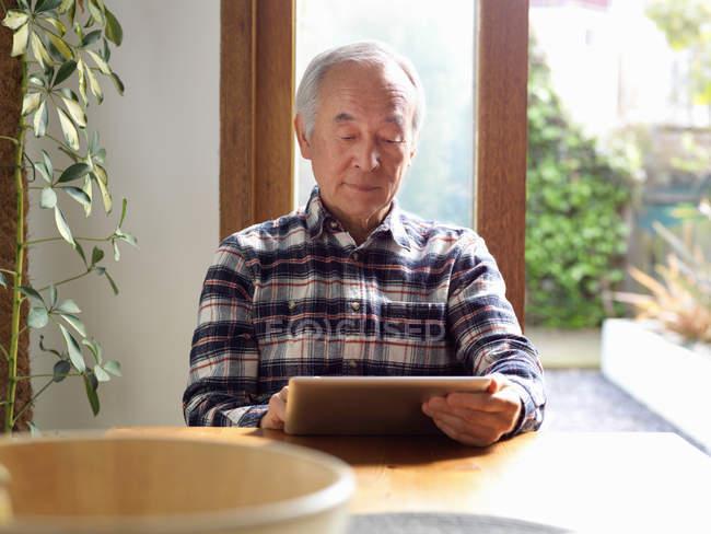 Older man using tablet computer — Stock Photo