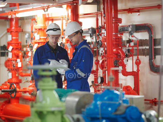 Інженери працюють разом у турбінний зал — стокове фото