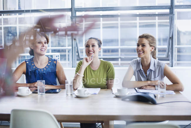 Mujeres sonrientes y escuchadoras en la presentación de la formación - foto de stock