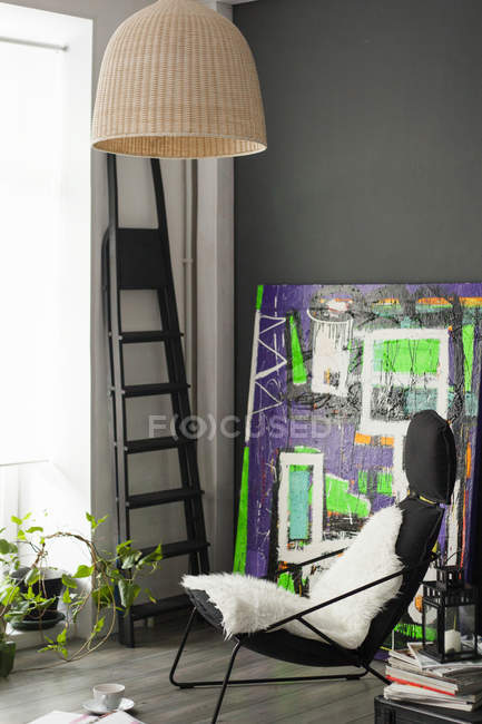 Сидящая комната с винтажным креслом и абстрактной живописью — стоковое фото