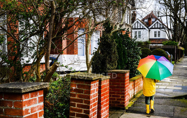 Rear view of boy in yellow anorak carrying umbrella along street — Stock Photo