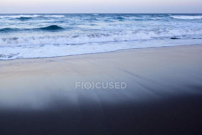 Vagues de mer sur la plage de sable au crépuscule — Photo de stock