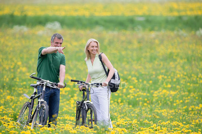 Couple riding bikes in field — Stock Photo