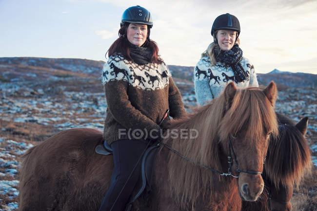 Mulheres montando cavalos ao ar livre — Fotografia de Stock