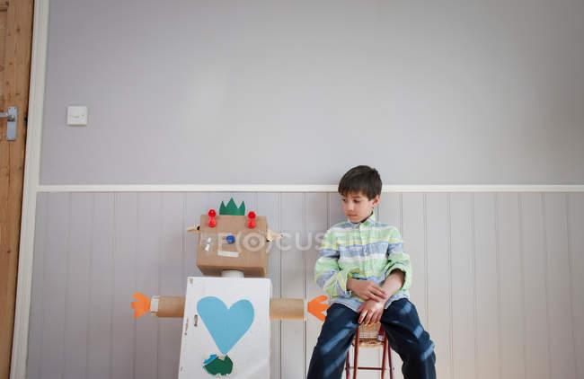 Junge sitzt neben selbstgebasteltem Spielzeugroboter — Stockfoto