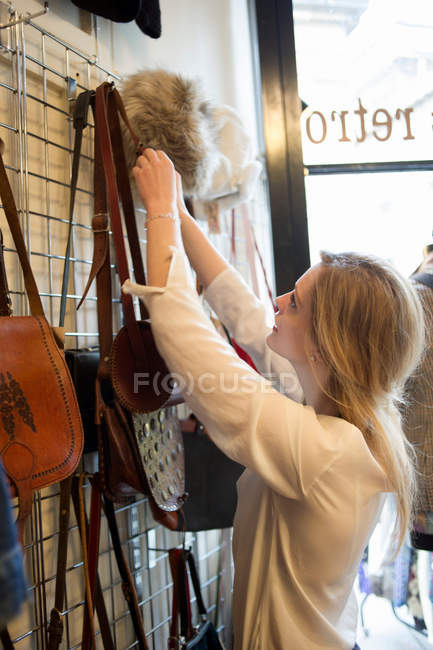 Woman hanging up bags in vintage clothes shop — стокове фото