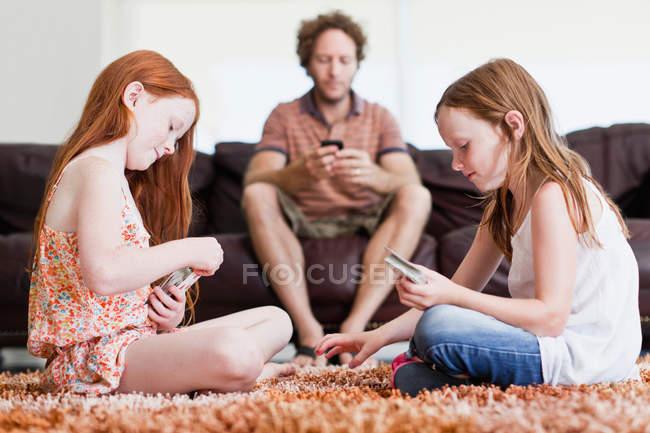 Девушки играют в карты на полу в гостиной — стоковое фото