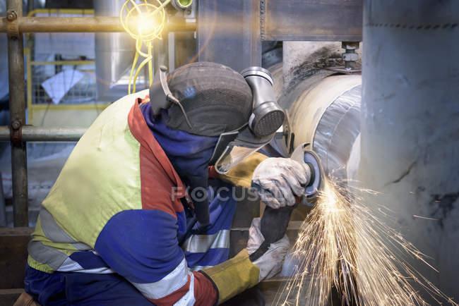 Arbeiter schleift Rohr in Gaskraftwerk — Stockfoto