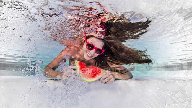 Vue sous-marine de la femme portant des lunettes de soleil, mangeant une tranche de melon d'eau, souriant — Photo de stock