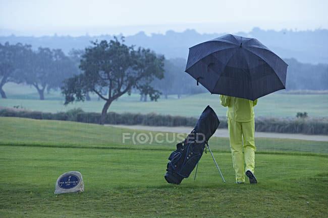 Vue arrière du golfeur à côté du sac de golf en parapluie — Photo de stock