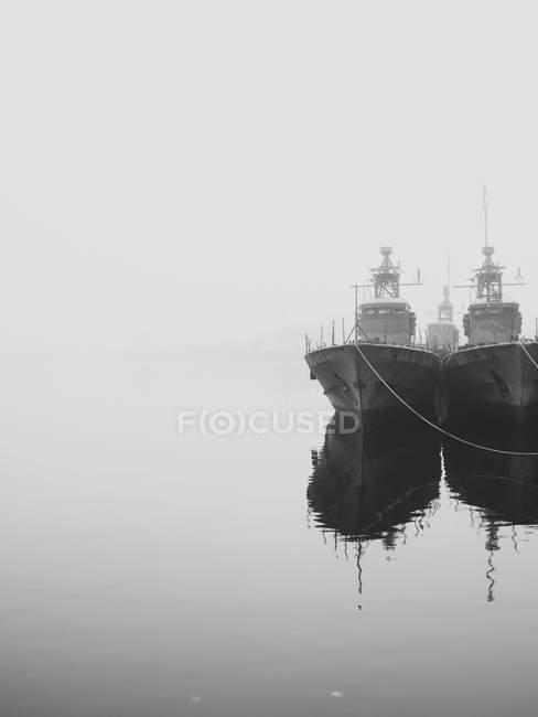 Ships docked in still harbor in mist — Stock Photo
