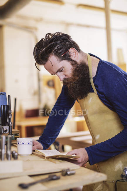 Mid adult craftsman checking notebook in organ workshop — Stock Photo