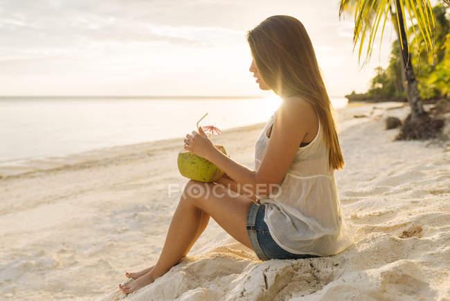 Молода жінка п'є кокосове молоко Анда пляж, провінція Бохол, Філіппіни — стокове фото