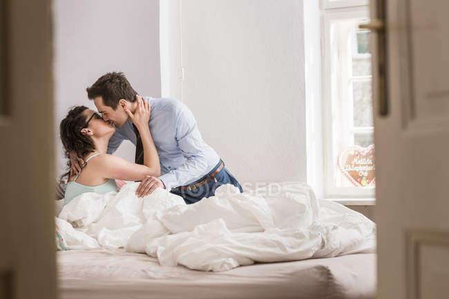Mi adulte couple baisers sur lit — Photo de stock