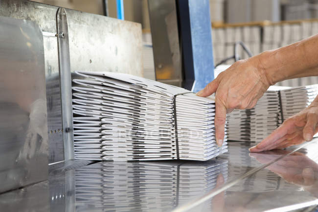Close up of female hands stacking cardboard packaging — Stock Photo