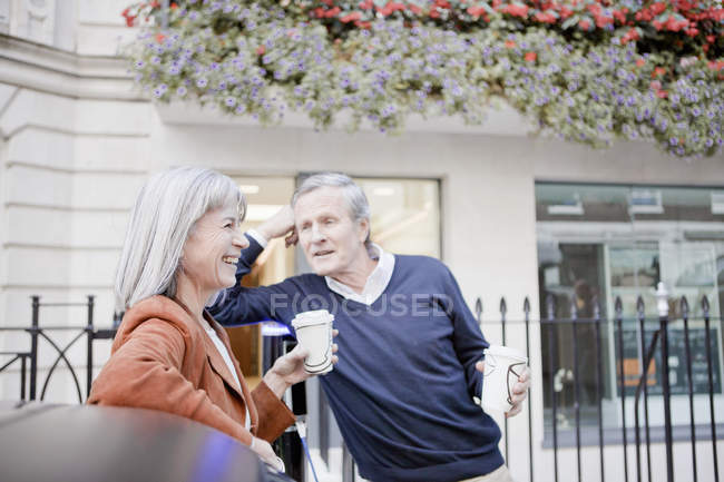 Couple drinking coffee on city street — Stock Photo