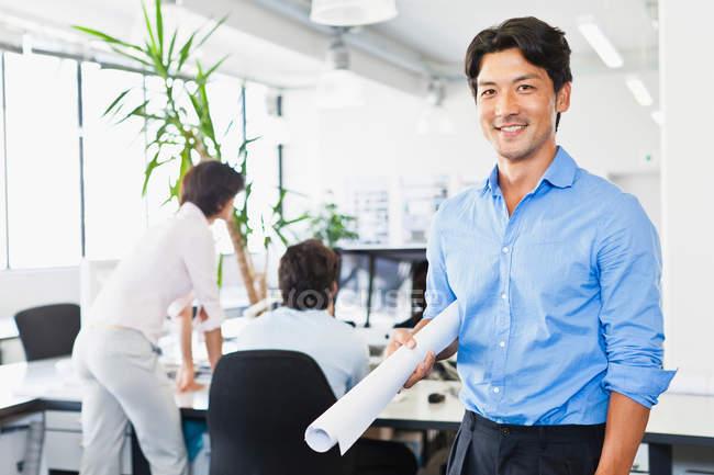 Бизнесмен с чертежами в офисе — стоковое фото