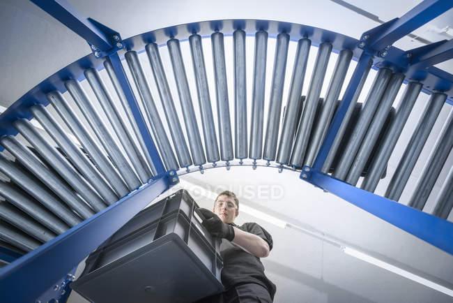 Vue à angle bas de l'apprenti avec la caisse sur la ligne de production — Photo de stock