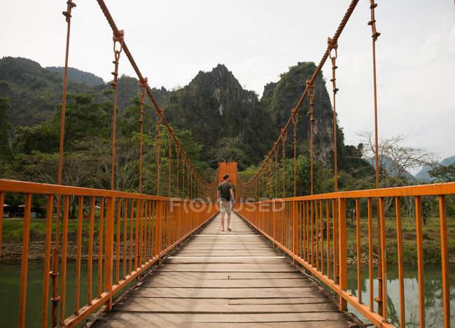 Hombre en el puente sobre el río, Vang Vieng, Laos - foto de stock