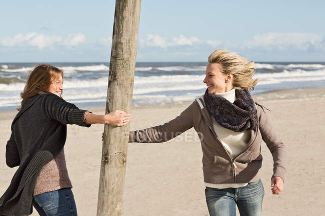 Donne sorridenti che giocano sulla spiaggia — Foto stock