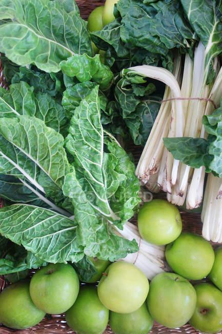 Vista superiore di mele verdi e foglie verdi in cestino — Foto stock