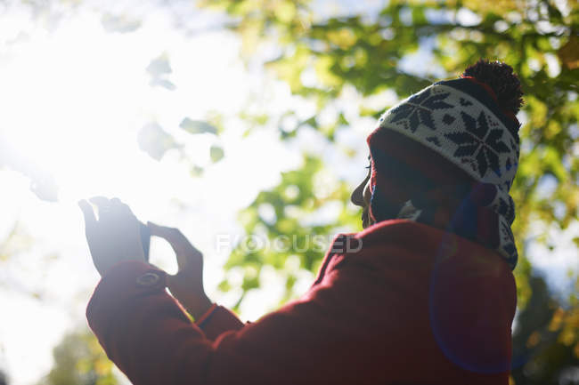 Mature woman photographing with camera phone in autumn park — Stock Photo