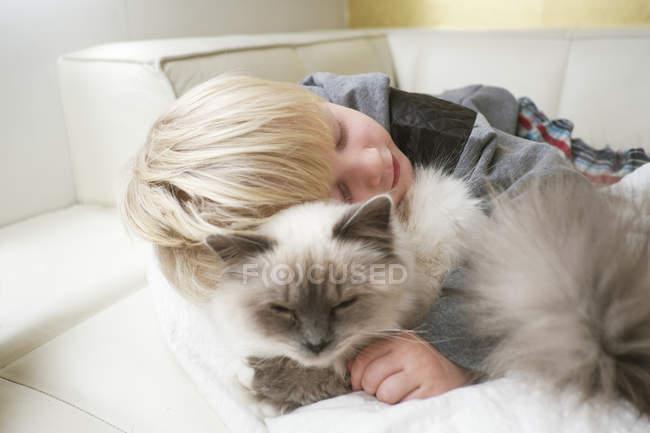 Carino bambino in età prescolare con gli occhi chiusi abbracciando gatto sul divano — Foto stock