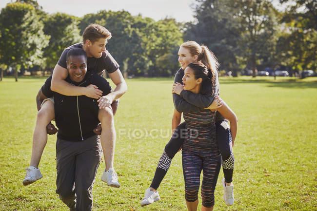 Hommes et femmes qui s'amusent à s'entraîner dans le parc, faisant une course de dos de cochon — Photo de stock