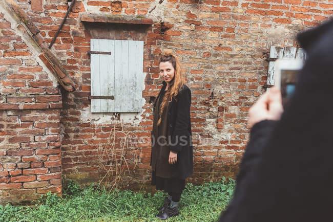 Sopra la spalla vista di uomo fotografare fidanzata da vecchio muro di mattoni — Foto stock