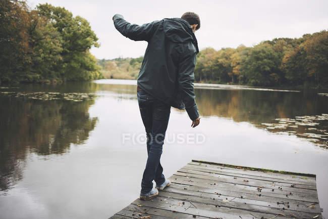 Jeune homme marchant le long du bord de la jetée — Photo de stock