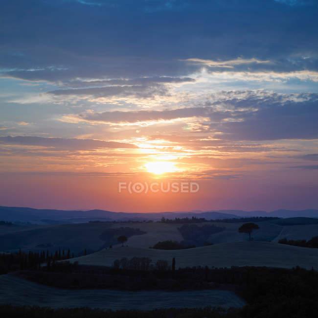 Pôr do sol sobre a paisagem rural — Fotografia de Stock