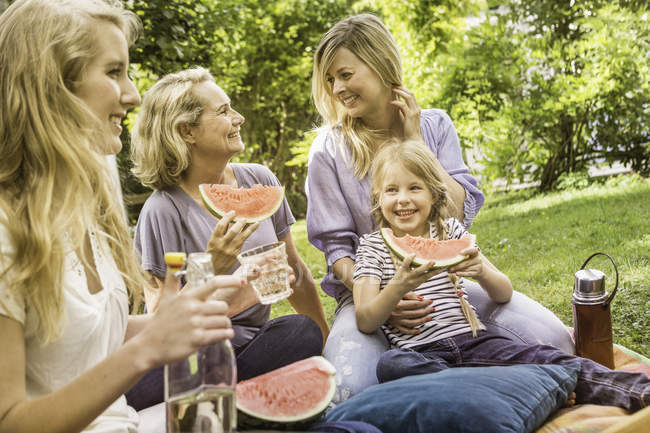 Three generation of women having picnic with watermelon — Stock Photo