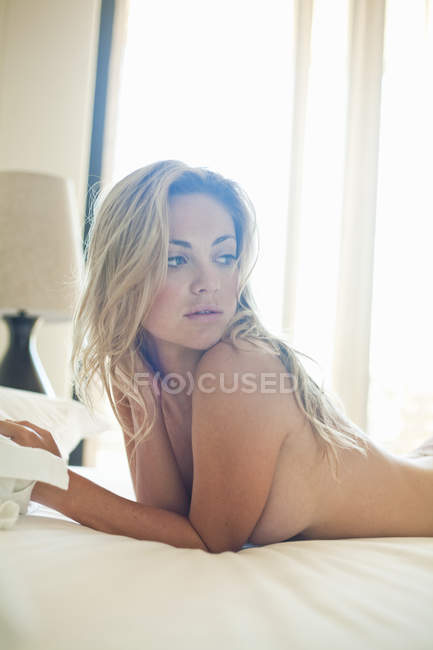 Nude young woman lying on bed — Stock Photo