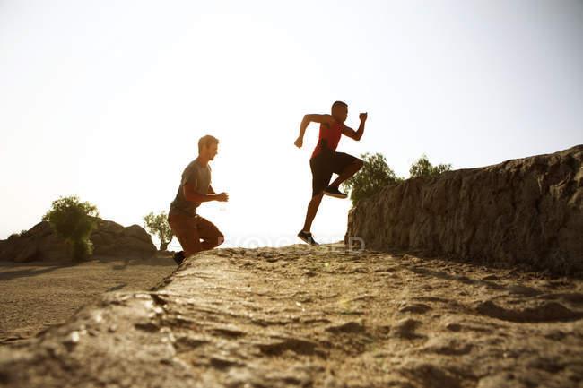 Dois amigos homens correndo juntos, ao ar livre — Fotografia de Stock