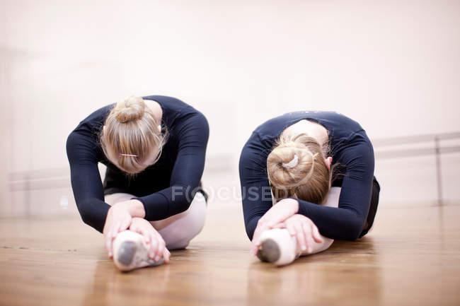 Ballerinas stretching on studio floor — Stock Photo