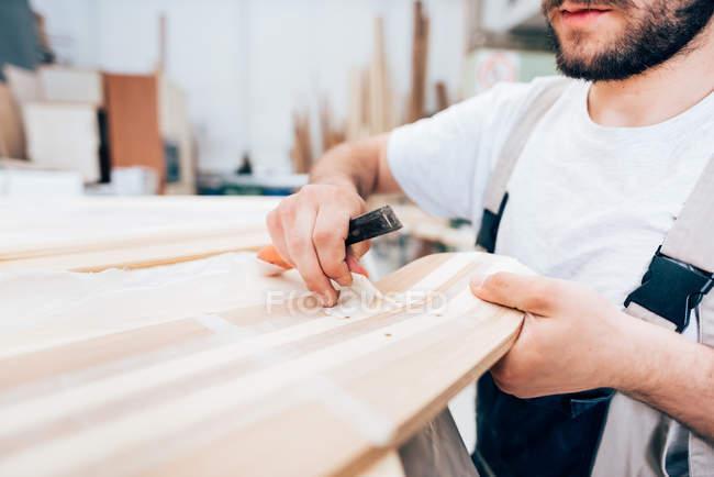 Молодой плотник за работой в мастерской — стоковое фото