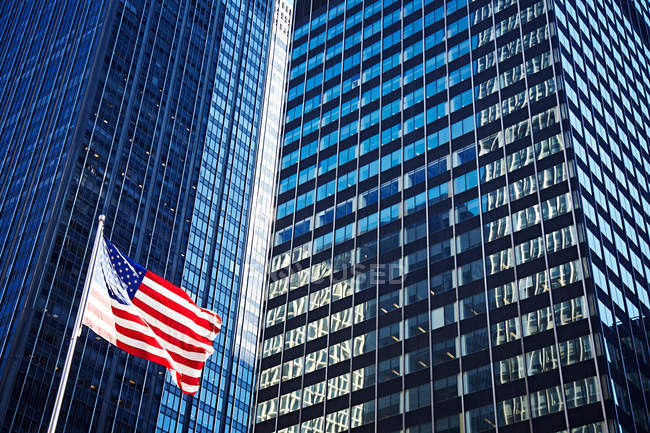 Skyscrapers exterior and US flag — Stock Photo