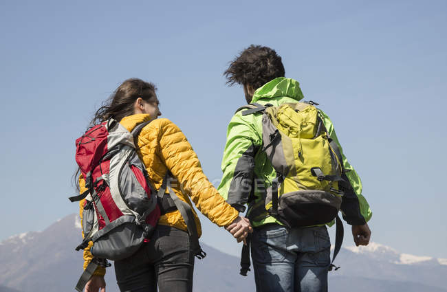 Rear view of hiking couple in front of snow capped mountain, Vogogna, Verbania, Piemonte, Italy — Stock Photo