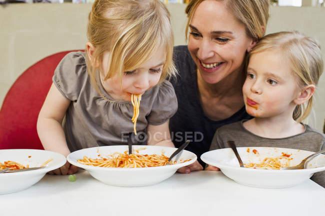 Взрослая мать ест спагетти с двумя маленькими дочерьми — стоковое фото
