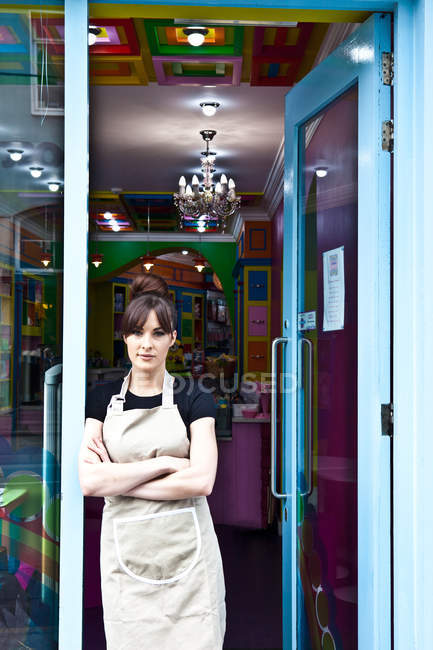 Portrait of female worker in cake shop, standing in doorway of shop, looking out — Stock Photo