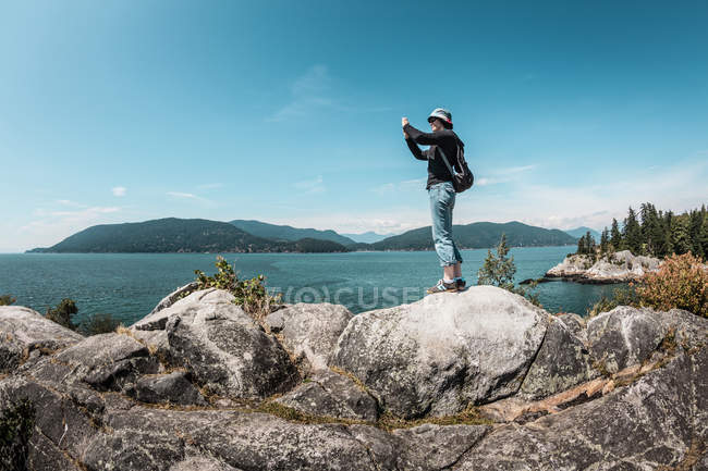 Woman taking pictures of rural lake — Stock Photo
