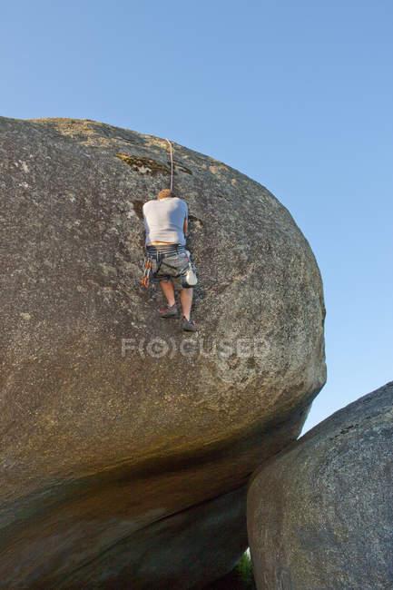 Заднього вигляду юнак сходження мотузками на Боулдер — стокове фото