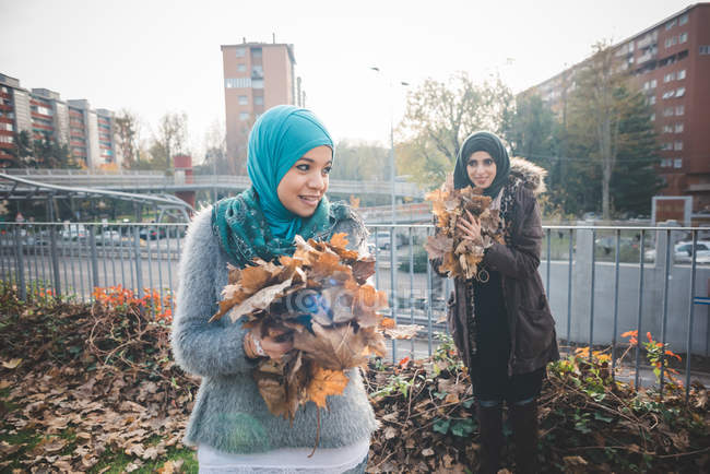 Two young women friends collecting autumn leaves in park — Stock Photo