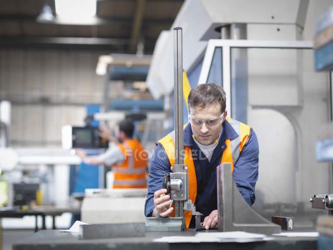 Arbeiter vermessen Teile in Blechfabrik — Stockfoto