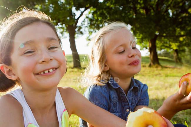 Lachende Mädchen essen Äpfel im Freien — Stockfoto