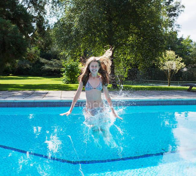 Fille sauter dans la piscine — Photo de stock