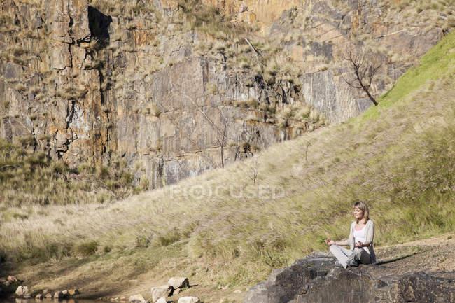 Junge Frau in Yogaposition auf Felsen am See — Stockfoto