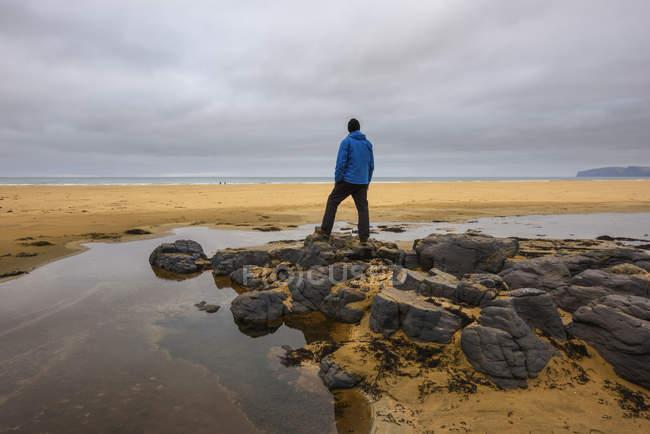 Uomo in piedi sulle rocce e guardando il paesaggio, vista posteriore — Foto stock