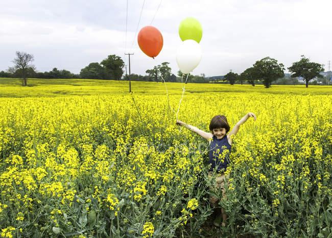Menino em pé no campo de flores amarelo segurando balões vermelhos, amarelos e brancos — Fotografia de Stock
